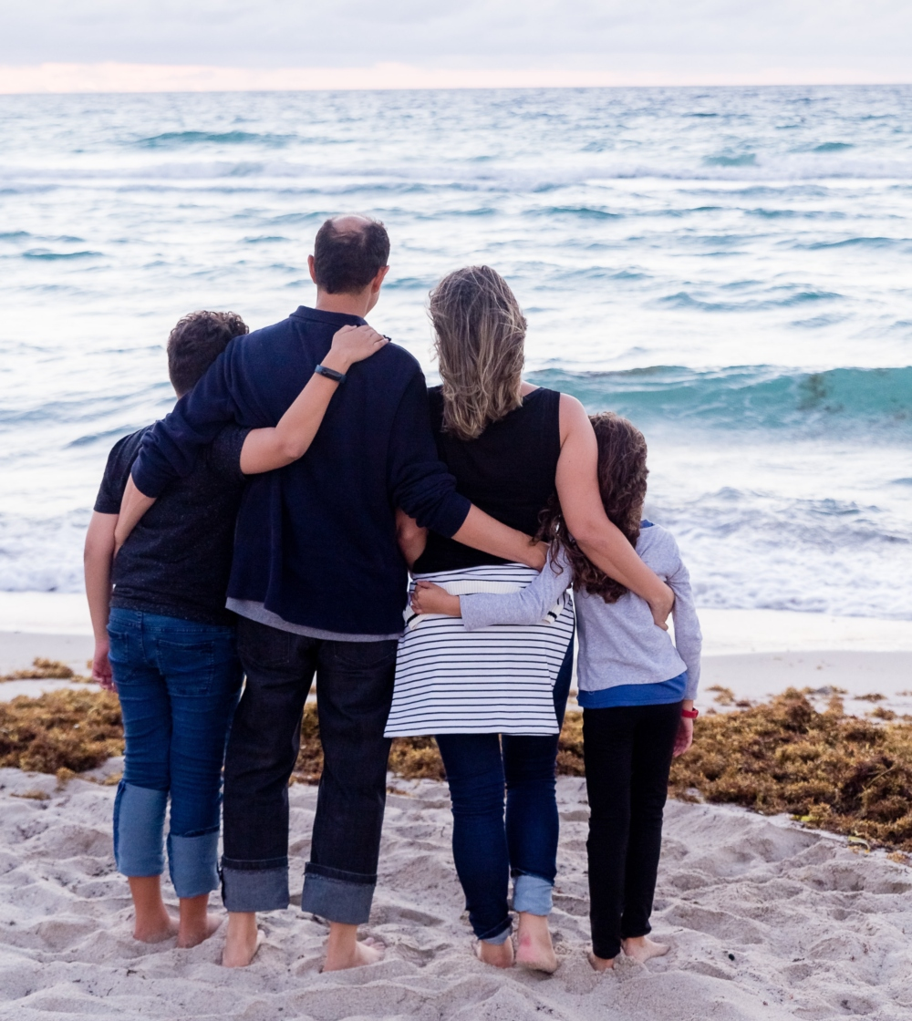 A family looks out to the sea together.